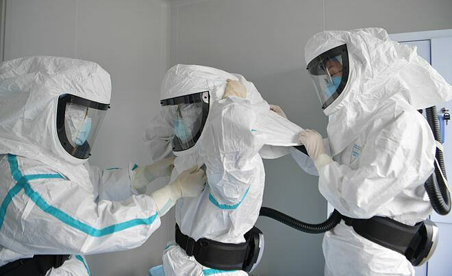 Nhóm nghiên cứu mặc đồ bảo hộ để tiến vào phòng thí nghiệm. Ảnh: Reuters