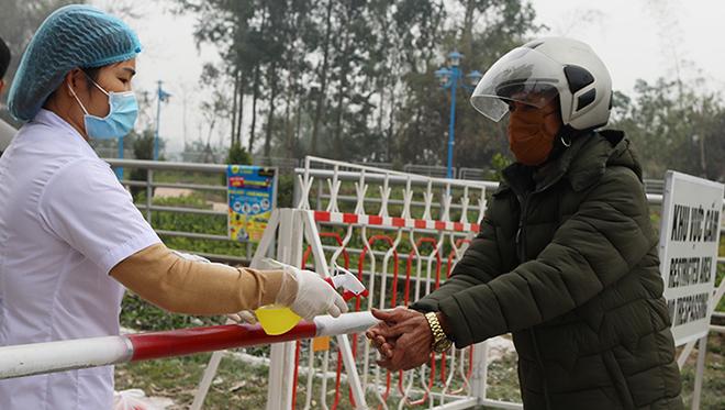 Người ra vào chốt kiểm dịch xã Sơn Lôi, Vĩnh Phúc, được nhân viên y tế xịt khử trùng tay phòng dịch. Ảnh: Ngọc Thành.