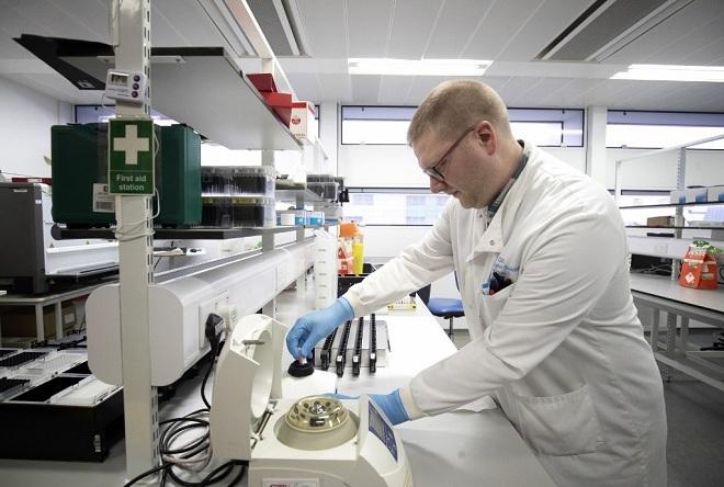 Kỹ thuật viên tạiBệnh viện Hoàng gia Glasgowtrích xuất virus từ các mẫu bệnh phẩm đểphân tích và xác định cấu trúc di truyền. Ảnh: AFP