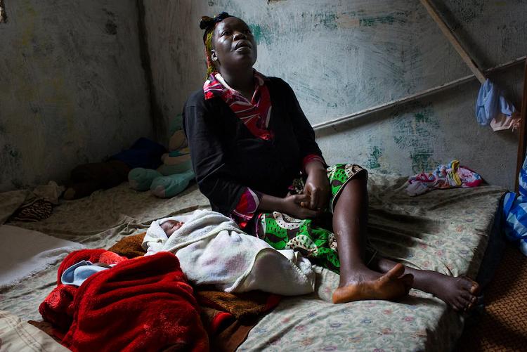 Một người phụ nữ và hai bésinh đôi ở Liberia đã phải vật lộn để được hỗ trợy tế trong vụ dịch Ebola 2014. Ảnh: Washington Post