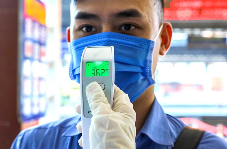 Đo nhiệt độ để phát hiện sốt, phòng ngừa Covid-19 tại TPHCM tháng 2. Ảnh: Quỳnh Trần.