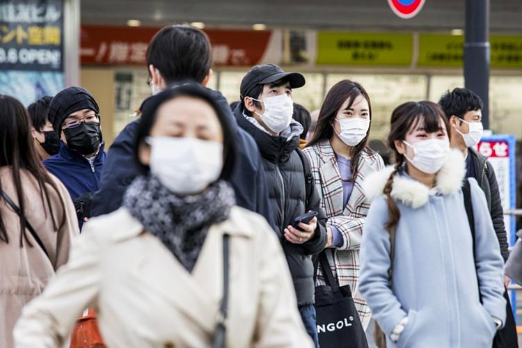 Người dân Tokyo đeo khẩu trang để phòng Covid-19 khi đi làm vào giờ cao điểm ngày 25/2. Ảnh: Bloomberg