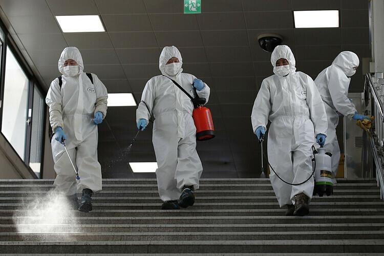 Công nhân tiêu độc khử trùng tại ga tàu điện ngầm ở Seoul, Hàn Quốc, ngày 13/3. Ảnh: AP