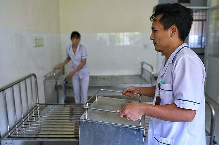 Nhân viên y tế hoàn thành việc chuẩn bị giường bệnh trong ngày 15/3. Ảnh: Hữu Khoa.