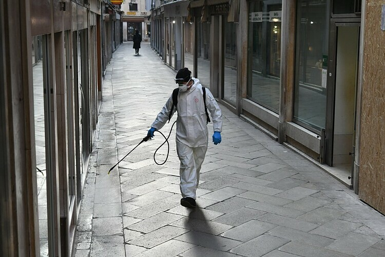Nhân viên y tế đang tiến hành tiêu độc khử trùng trên đường phố Venice, Italy ngày 11/3. Ảnh: AFP