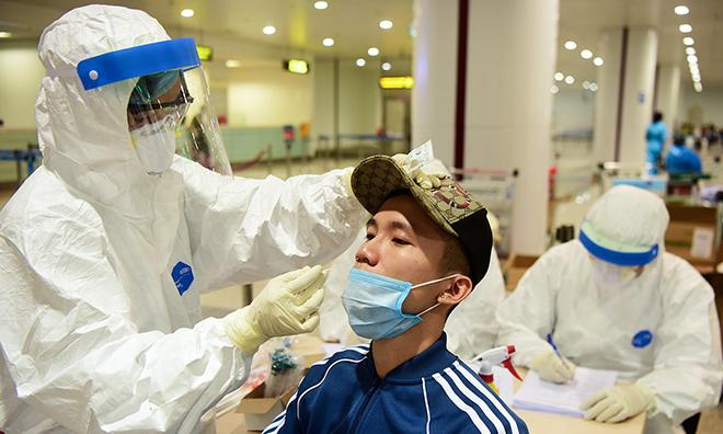 Nhân viên y tế tiến hành xét nghiệm những người trở về từ vùng dịch ngay tại sân bay Nội Bài ngày 18/3. Ảnh: Giang Huy