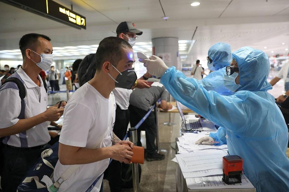 Đo thân nhiệt hành khách nhập cảnh tại sân bay Tân Sơn Nhất ngày 17/3. Ảnh: Hữu Khoa.