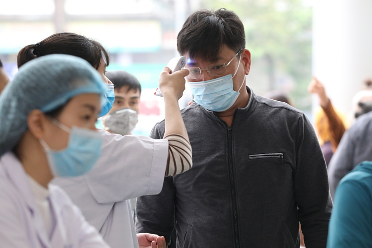 Nhân viên y tế bệnh viện Kđonhiệt độ bệnh nhân, người nhà bệnh nhân. Ảnh: Ngọc Thành.