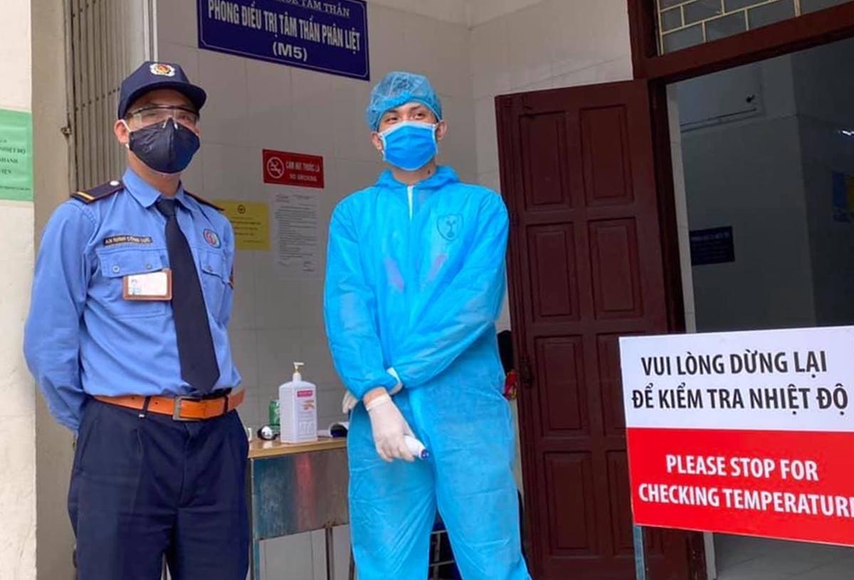 Nhân viên y tế trực đo thân nhiệt bệnh nhân tại khoa Tâm thần, Bệnh viện Bạch Mai, ngày 21/3. Ảnh: L.N.