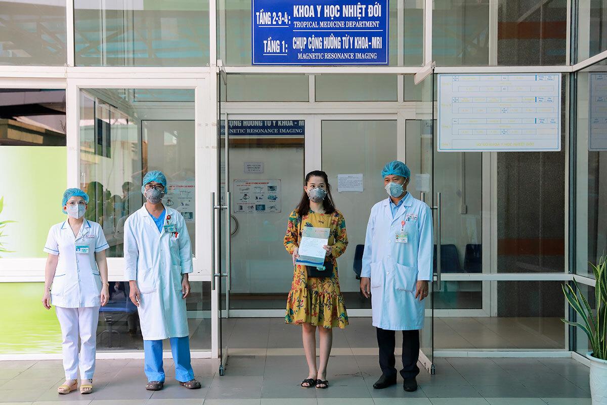 Lãnh đạo Bệnh viện Đà Nẵng trao giấy xuất viện cho bệnh nhân 35. Ảnh: Nguyễn Đông.