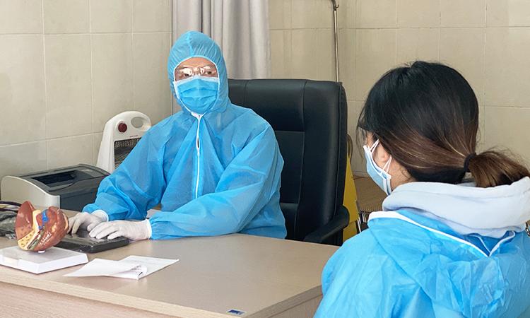 Bác sĩ bệnh viện Đống Đa, Hà Nội đang thăm khám, sàng lọc sức khỏe bệnh nhân nghi nhiễm. Ảnh: Thùy An