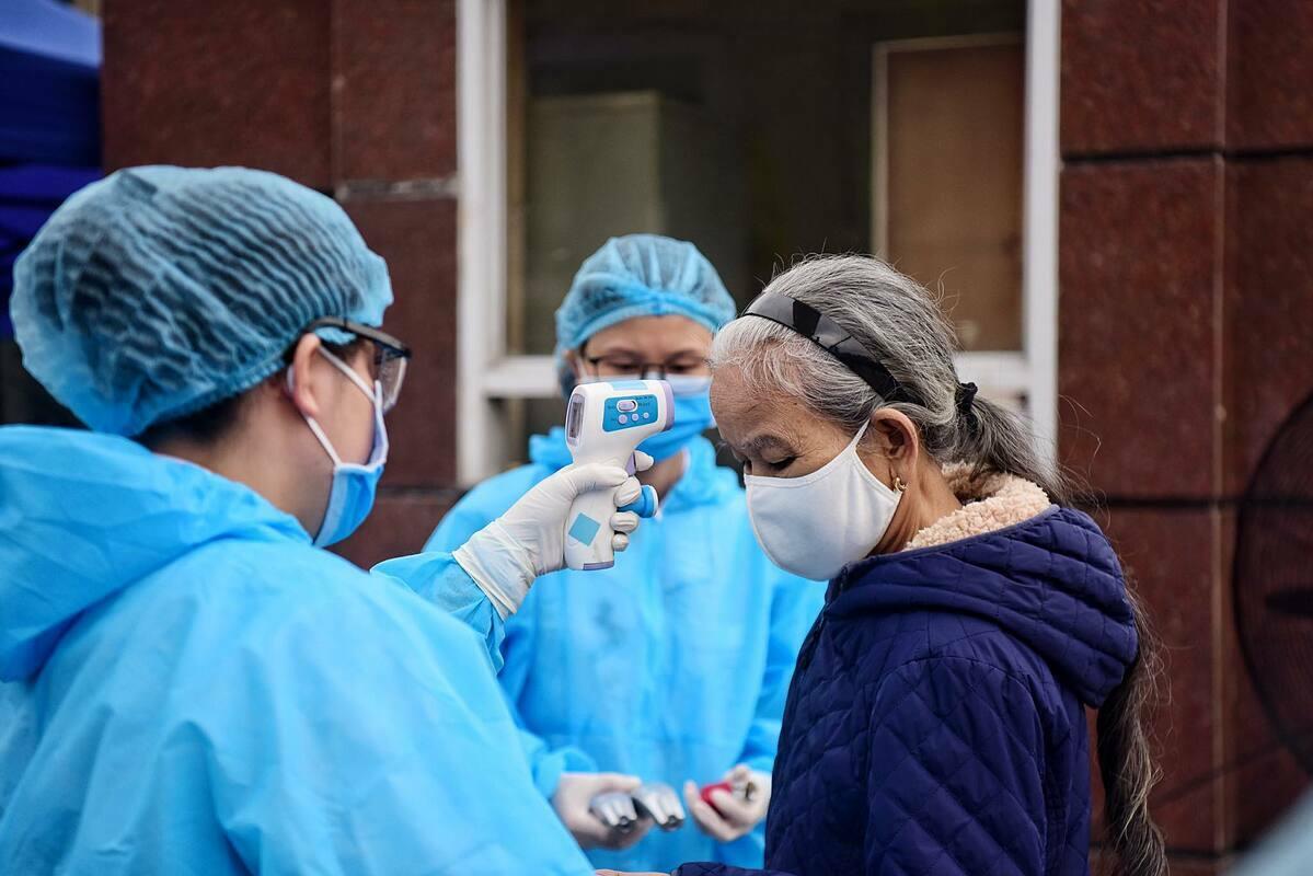Nhân viên y tế đo thân nhiệt ngừoi vào Bệnh viện Bạch Mai snags 28/3. Ảnh: Giang Huy.