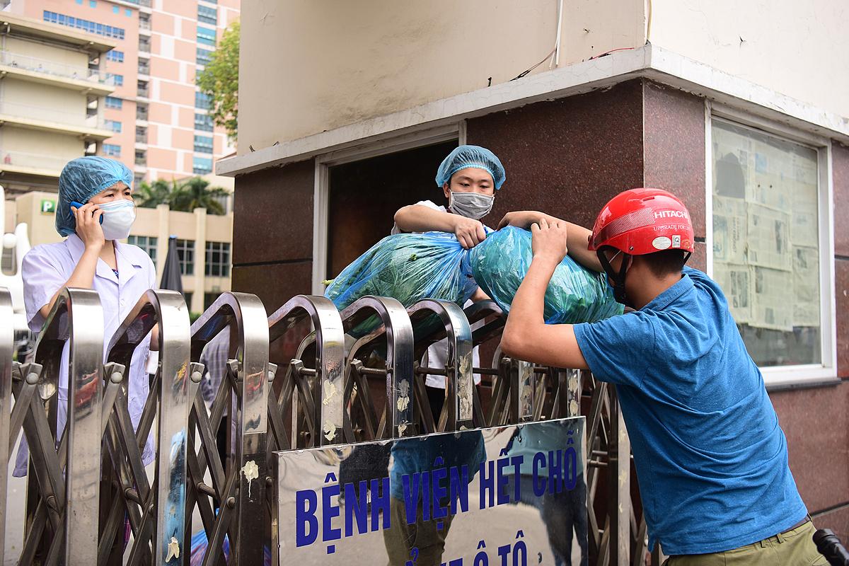 Người bên ngoài tiếp tế đồ ăn cho người bên trong bệnh viện sau lệnh phong toả của Bệnh viện Bạch Mai. Ảnh: Giang Huy.