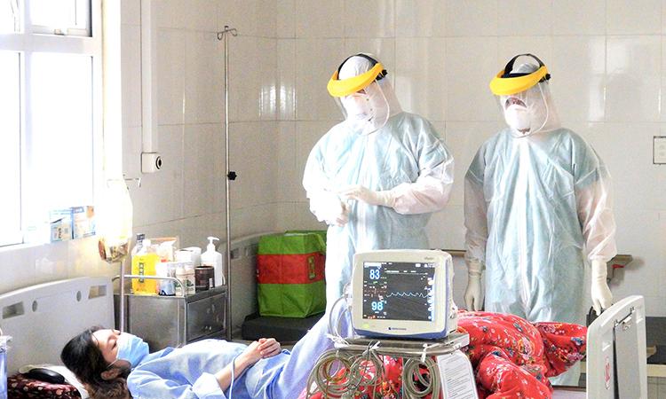 Bác sĩ Hùng (ở giữa) đang trực tiếp kiểm tra, thăm hỏi tình hình sức khỏe bệnh nhân 50. Ảnh: Bệnh viện cung cấp