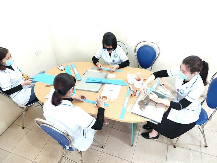 Nhóm điều dưỡng cũng nhau làm mũ cống giọt bắn tại Bệnh viện Đa khoa Hòa Bình ngày 2/4. Ảnh: Nguyễn Tuyết