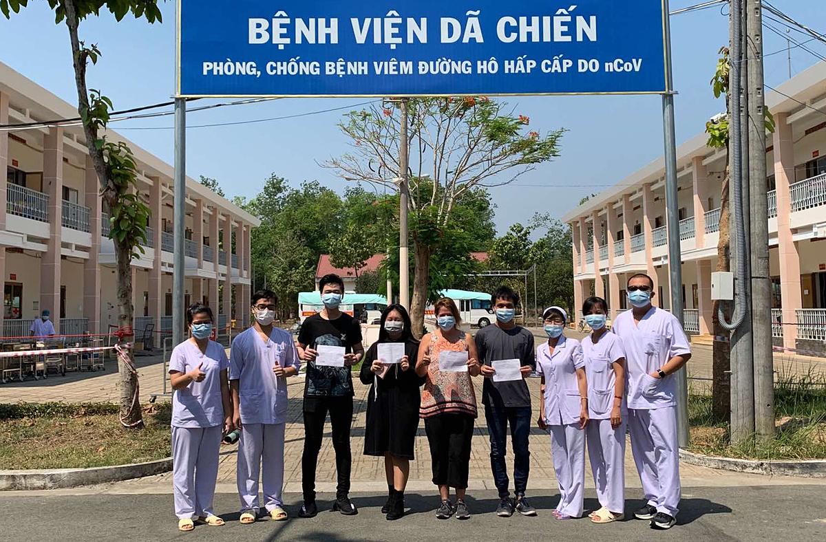 3 bệnh nhân chụp hình lưu niệm cùng bác sĩ, cán bộ Bệnh viện Dã chiến Củ Chi trước khi rời viện. Ảnh do bệnh viện cung cấp.