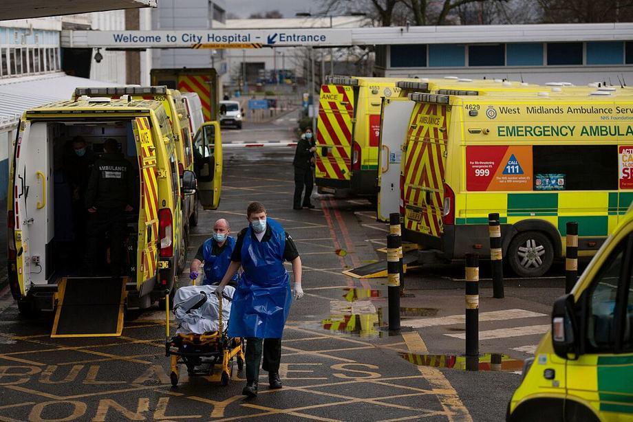 Nhân viên cấp cứu vận chuyển người mắc Covid-19 đến Bệnh viện Thành phố Birmingham, Anh, ngày 12/1. Ảnh: AP